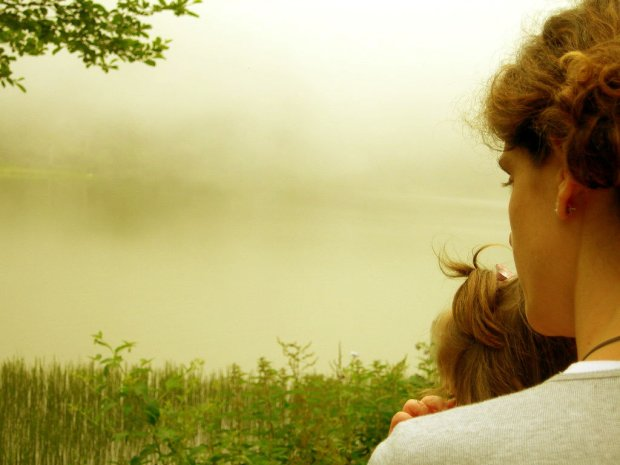 Mother and child gazing at a misty pond